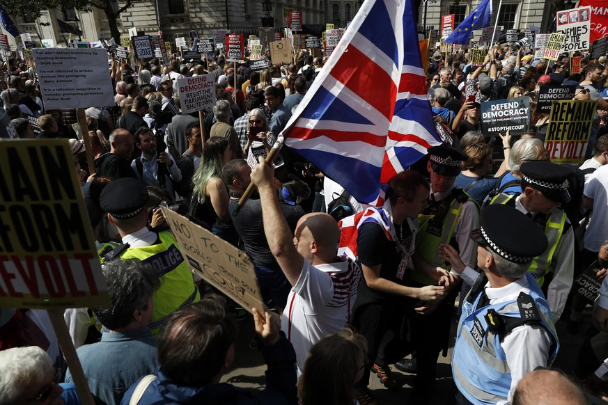 Brexit supporters surrounded by policemen hold British flags as anti Brexit protesters demonstrate during a rally outside Downing Street in London, Saturday, Aug. 31, 2019. Political opposition to Prime Minister Boris Johnson's move to suspend Parliament is crystalizing, with protests around Britain and a petition to block the move gaining more than 1 million signatures. (AP Photo/Alastair Grant)
