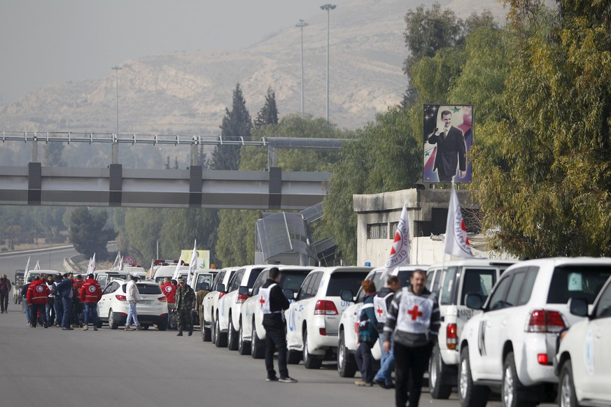 A convoy consisting of Red Cross, Red Crescent and United Nation (UN) gather before heading towards to Madaya from Damascus, and to al Foua and Kefraya in Idlib province, Syria January 11, 2016. Aid convoys headed for a besieged Syrian town where thousands are trapped and the United Nations says people are reported to have died of starvation. Trucks headed for Madaya, near the Lebanese border, and two villages in the northwest of the country on Monday, the Red Cross said, as part of an agreement between warring sides. REUTERS/Omar Sanadiki        TPX IMAGES OF THE DAY