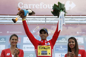 epa04388185 Spanish cyclist of Tinkoff Saxo team Alberto Contador, celebrates on the podium aftyer retaining the overall leader's red jersey after the 14th stage of the Vuelta a Espana cycling race, over 200.8 km from Santander to La Camperona, northern Spain, 06 September 2014.  EPA/JAVIER LIZON