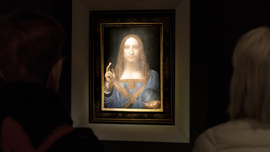 epa06331563 People look at the painting 'Salvator Mundi' by Leonardo da Vinci (circa 1500) during a public preview before an auctioning of the painting tonight at Christie's auction house in New York, New York, USA, 15 November 2017. The painting is reportedly one of only twenty paintings by Da Vinci and is expected to sell for at least 100 million USD.  EPA/JUSTIN LANE