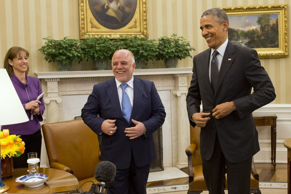 Iraqi Prime Minister Haider Al-Abadi and President Barack Obama fix their suit jackets as they finish their meeting in the Oval Office of the White House in Washington, Tuesday, April 14, 2015. The Prime Minister's visit is to discuss U.S.-Iraq policy and the fight against the IS group. (AP Photo/Jacquelyn Martin)