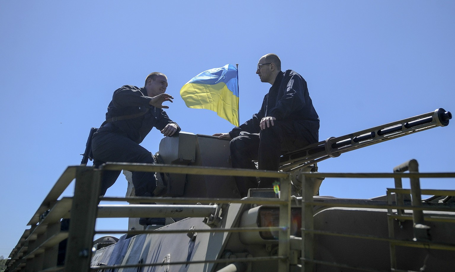Ukraine's Prime Minister Arseny Yatseniuk (R) talks to a security personnel member on a military vehicle as he arrives to inspect the Ukrainian military grouping near Slaviansk in eastern Ukraine May 7, 2014. REUTERS/Andrew Kravchenko/Pool (UKRAINE - Tags: POLITICS MILITARY)