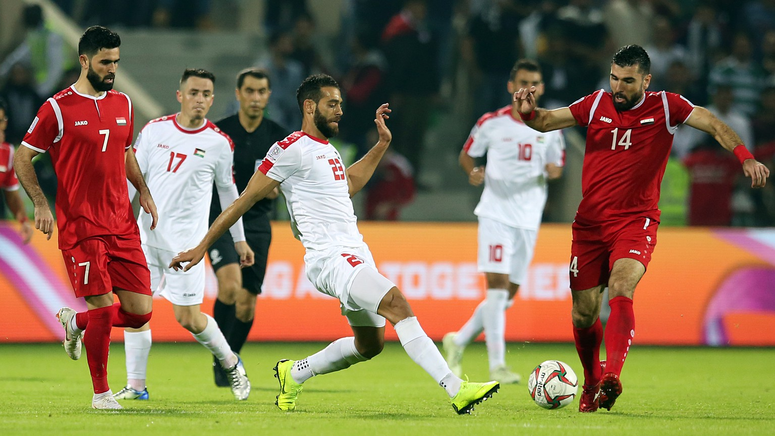 epa07265804 Tamer Hag Mohamad (R) of Syria in action against Mohammed Darwish (C) of Palestine during the 2019 AFC Asian Cup group B preliminary round match between Syria and Palestine in Sharjah, United Arab Emirates, 06 January 2019.  EPA/MAHMOUD KHALED