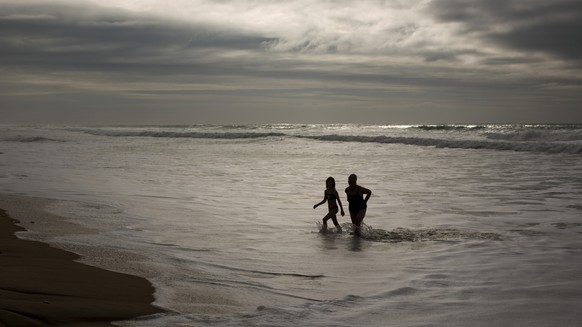 Two German tourists walk on the seashore after swimming at the Atlantic ocean in a beach in Cadiz, southwest Spain, on Wednesday, Jan. 1, 2014. (AP Photo/Emilio Morenatti)