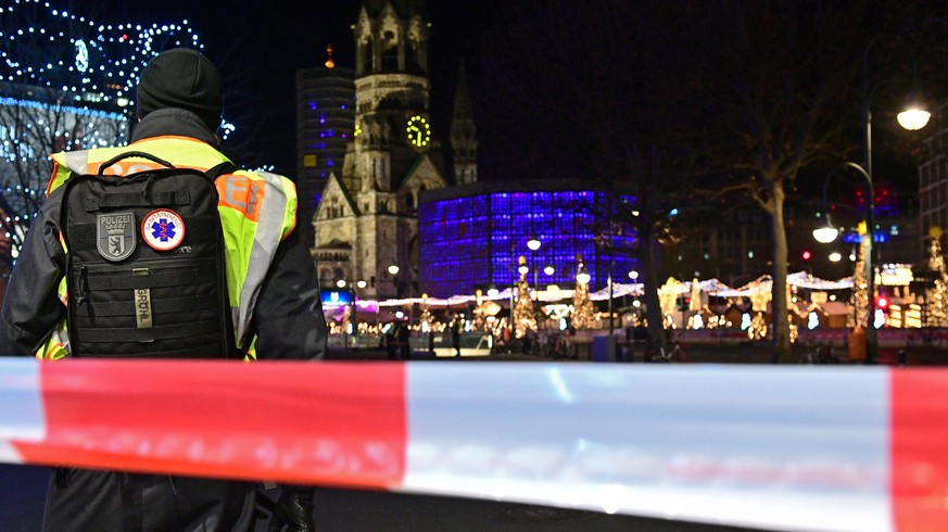 epa08085915 A policeman with a backpack reading 'medical service' stands in front of the Kaiser-Wilhelm-Gedaechtniskirche memorial church with the Christmas market on Breitscheidplatz square in Berlin, Germany, 21 December 2019. A suspicious object was found and the Christmas market evacuated afterwards. In 2016, the place was the target of a terror attack in which 12 people died.  EPA/CLEMENS BILAN