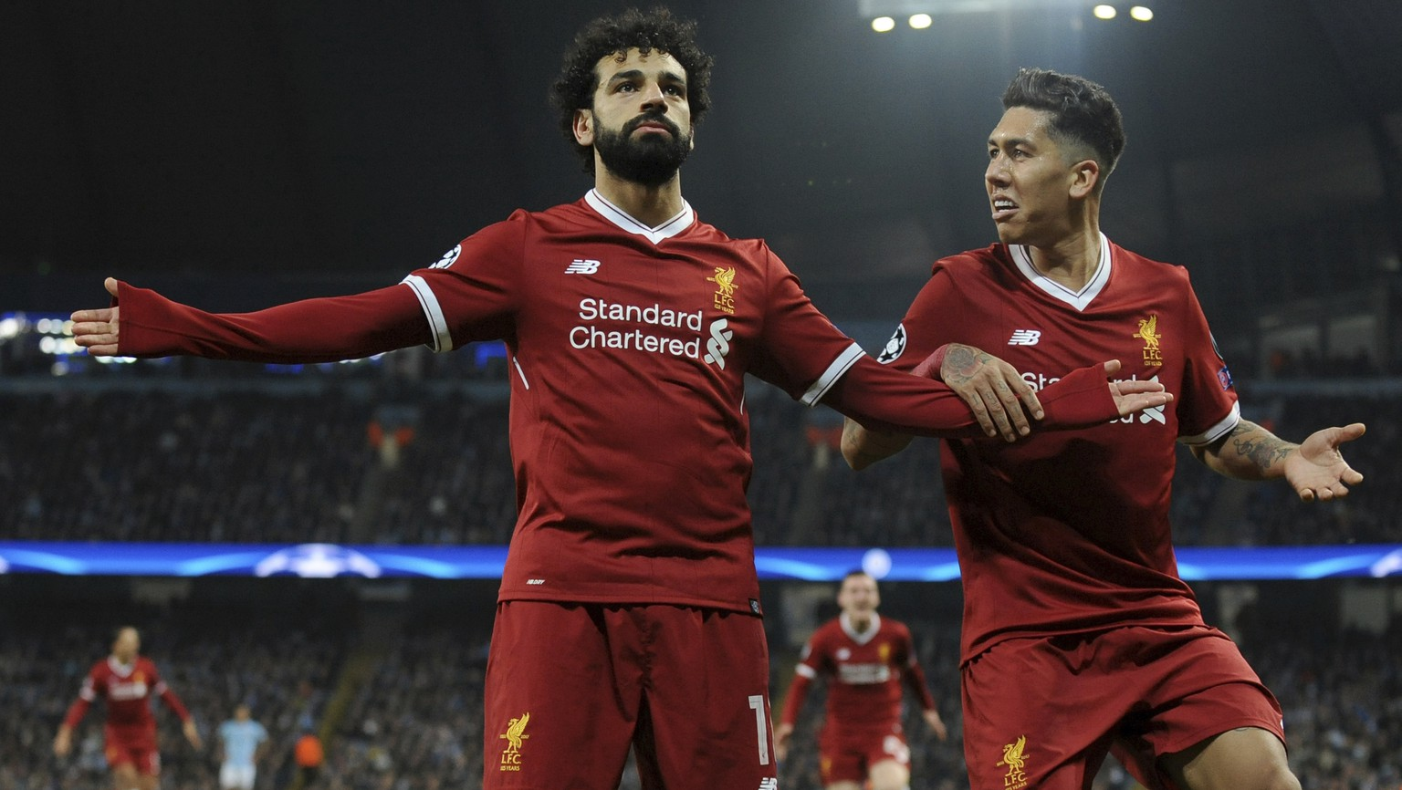 Liverpool's Mohamed Salah, left, celebrates scoring his side's first goal with Liverpool's Roberto Firmino during the Champions League quarterfinal second leg soccer match between Manchester City and Liverpool at Etihad stadium in Manchester, England, Tuesday, April 10, 2018. (AP Photo/Rui Vieira)