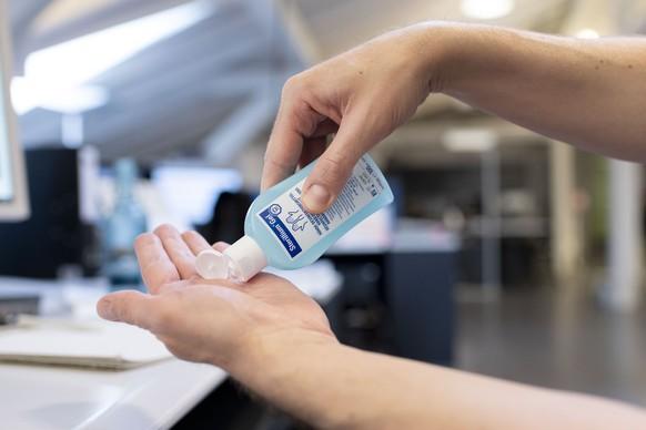 [Gestellte Aufnahme / Symbolbild] Eine Person desinfisziert am Arbeitsplatz die Haende mit einem Handdesinfektionsmittel, fotografiert am 2. Maerz 2020 in Zuerich. (KEYSTONE/Christian Beutler)