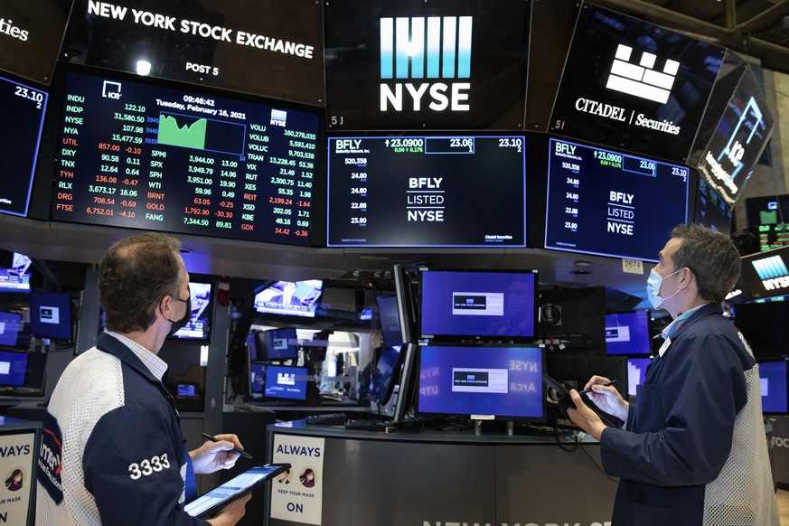 In this photo provided by the New York Stock Exchange, traders Robert Charmak, left, and Gregory Rowe, work on the trading floor, Tuesday, Feb. 16, 2021. Stocks were modestly higher in morning trading Tuesday, pushed by energy companies who have seen record electricity prices due to the frigid cold impacting much of the country. (Nicole Pereira/New York Stock Exchange via AP)