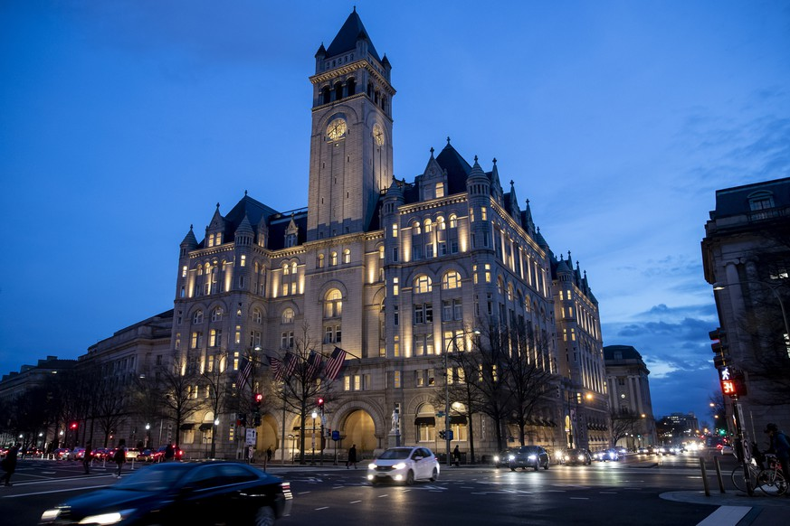 FILE - In this Jan. 23, 2019, file photo, the Trump International Hotel near sunset in Washington. A federal appeals court will reconsider a ruling from a three-judge panel that threw out a lawsuit accusing President Donald Trump of illegally profiting off the presidency through his luxury Washington hotel. The Richmond-based 4th U.S. Circuit Court of Appeals agreed Tuesday, Oct. 15, to hold a hearing before the full court of 15 judges. Arguments are scheduled for Dec. 12. (AP Photo/Alex Brandon, File)