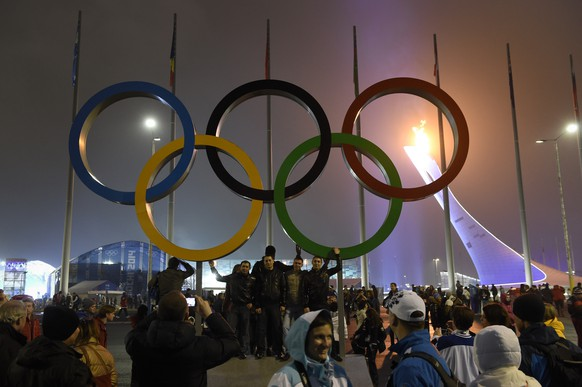 Visitors walk and stand in front of the Olympic rings and the Olympic cauldron in the Olympic Park at the XXII Winter Olympics 2014 Sochi in Sochi, Russia, on Sunday, February 16, 2014. (KEYSTONE/Laurent Gillieron)