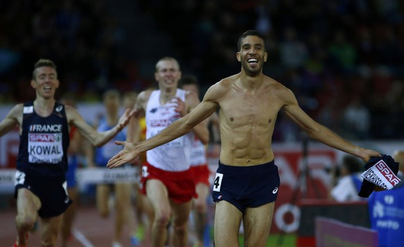 Mahiedine Mekhissi-Benabbad of France crosses the finish line with his vest in his hand, to win the men's 3000 metres steeplechase final during the European Athletics Championships at the Letzigrund Stadium in Zurich August 14, 2014.                    REUTERS/Arnd Wiegmann (SWITZERLAND  - Tags: SPORT ATHLETICS)