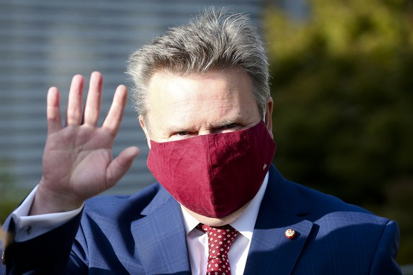 Vienna Mayor Michael Ludwig with face mask from the Social Democrats, SPOE, waves before entering a polling station to the local elections in Vienna, Austria, Sunday, Oct. 11, 2020. (AP Photo/Ronald Zak)