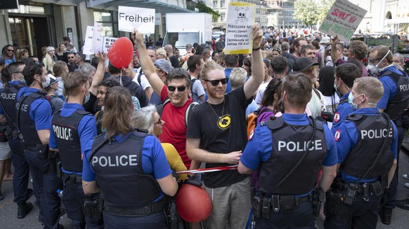 Polizisten halten Absperrbaender, um Demonstranten vom Bundesplatz fernzuhalten, bei einer Demonstration gegen den Coronavirus Lockdown, am Samstag, 9. Mai 2020 in Bern. (KEYSTONE/Peter Klaunzer)