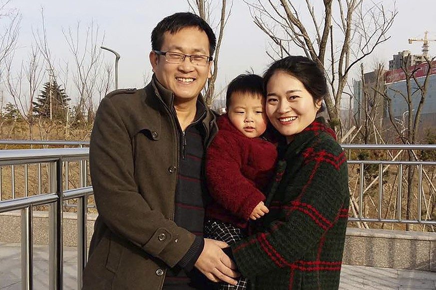 In this Feb. 2015, photo released by Li Wenzu, Wang Quanzhang, left, and his wife Li Wenzu poses for a photo with their son at a park in eastern China's Shandong province. About two dozen plainclothes police are stationed Wednesday Dec. 26, 2018, outside a courthouse in northern China as the trial of Wang, a prominent human rights lawyer was expected to unfold. Wang is among more than 200 lawyers and legal activists who were detained in a sweeping 2015 crackdown. The advocate for the banned Falun Gong meditation sect was charged with subversion of state power in 2016. He has been held without access to his lawyers or family for more than three years. (Wang Quanxiu via AP)
