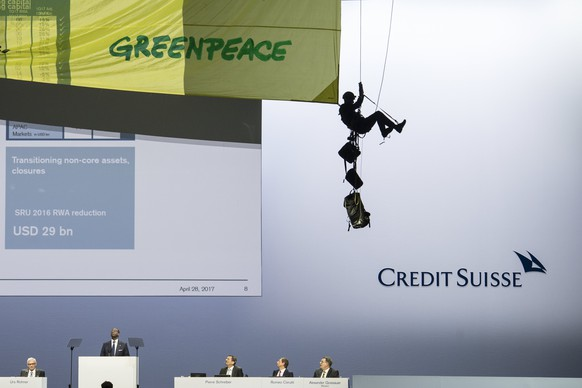 epa05932367 A Greenpeace activist abseils from the ceiling during the Credit Suisse (CS) general assembly in protest against the bank's pipline deals, at the Hallenstadion in Zurich, Switzerland, 28 April 2017. The activists brought a pipeline tube with them to protest what they call 'dirty pipeline deals' of the bank. The meeting was target of Greenpeace environment protection activists who brought a pipeline tube with them to protest what they call 'dirty pipeline deals' of the bank.  EPA/ENNIO LEANZA