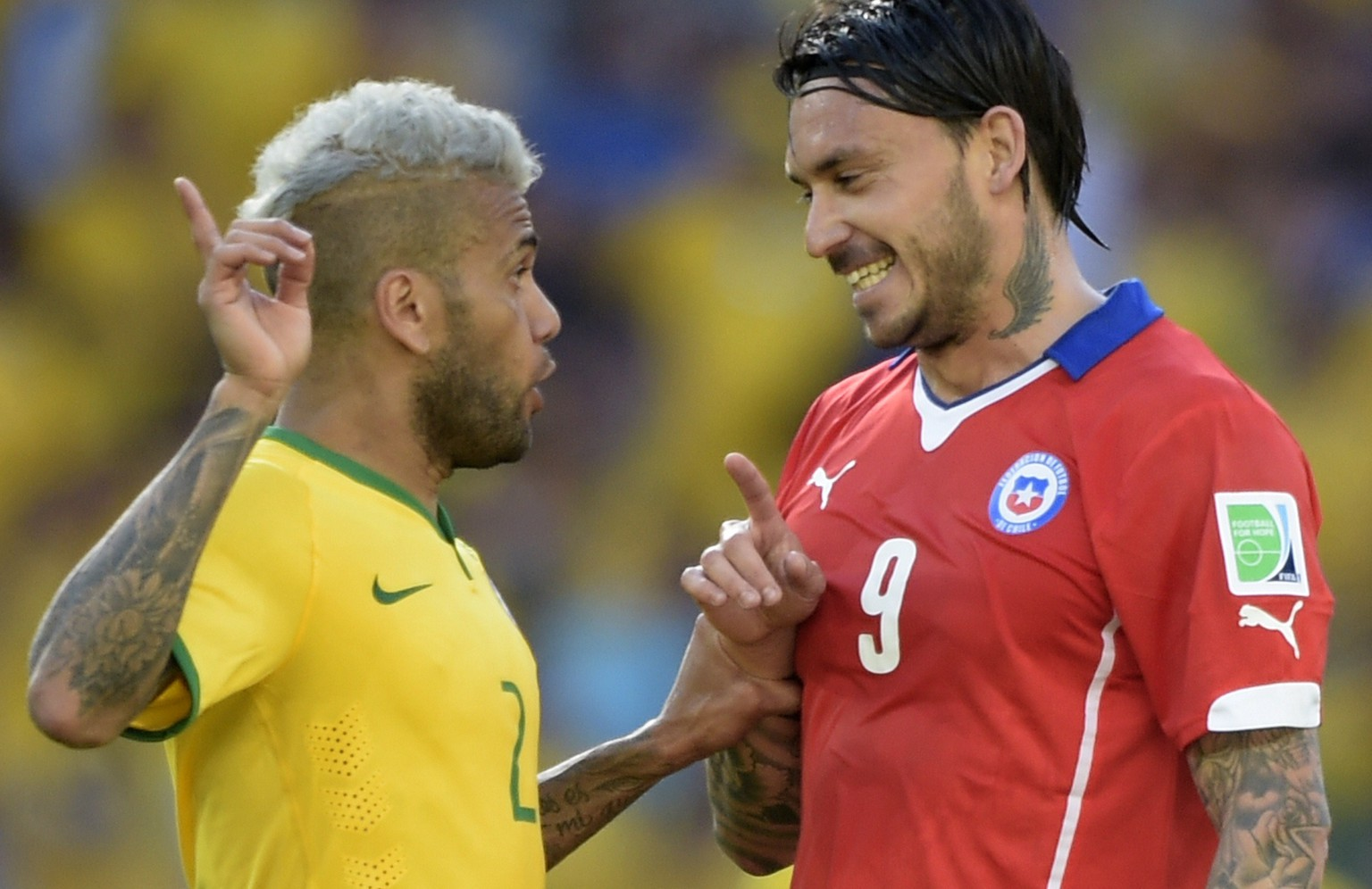 Brazil's defender Dani Alves (L) gestures towards Chile's forward Mauricio Pinilla during the Round of 16 football match between Brazil and Chile at The Mineirao Stadium in Belo Horizonte on June 28, 2014, during the 2014 FIFA World Cup. AFP PHOTO / JUAN MABROMATA