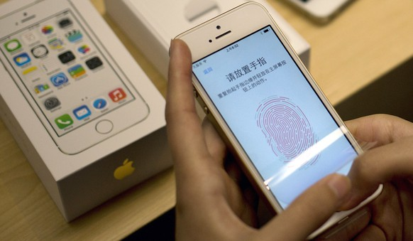 FILE - The Sept. 20, 2013 file photo shows a customer configuring the fingerprint scanner technology built into iPhone 5S at an Apple store in Wangfujing shopping district in Beijing. Soaring sales of iPhones in China, Russia, India and Brazil during the April-June 2014 period helped Apple overcome softening demand for the device in the U.S. and Europe, where consumers seem to be more interested in waiting for the autumn release of a new iPhone that's expected to feature a larger screen. (AP Photo/Andy Wong, File)