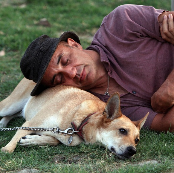 A man takes a nap with his dog on the lawn during the Daniel Pearl Day of Music marking the 10th anniversary of the Sept. 11 attacks in the US, in Taipei, Taiwan, Sunday, Sept. 11, 2011. (AP Photo/Chiang Ying-ying)