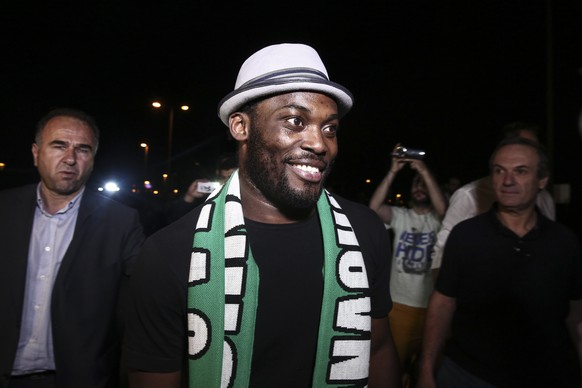 AC Milan midfielder Michael Essien,center, smiles upon his arrival at the Athens International Airport, in Athens, Greece, Monday, June 1, 2015. The 32-year-old Ghanaian player is set to undergo medical tests before potentially signing for the Greek club. (AP Photo/Yorgos Karahalis)