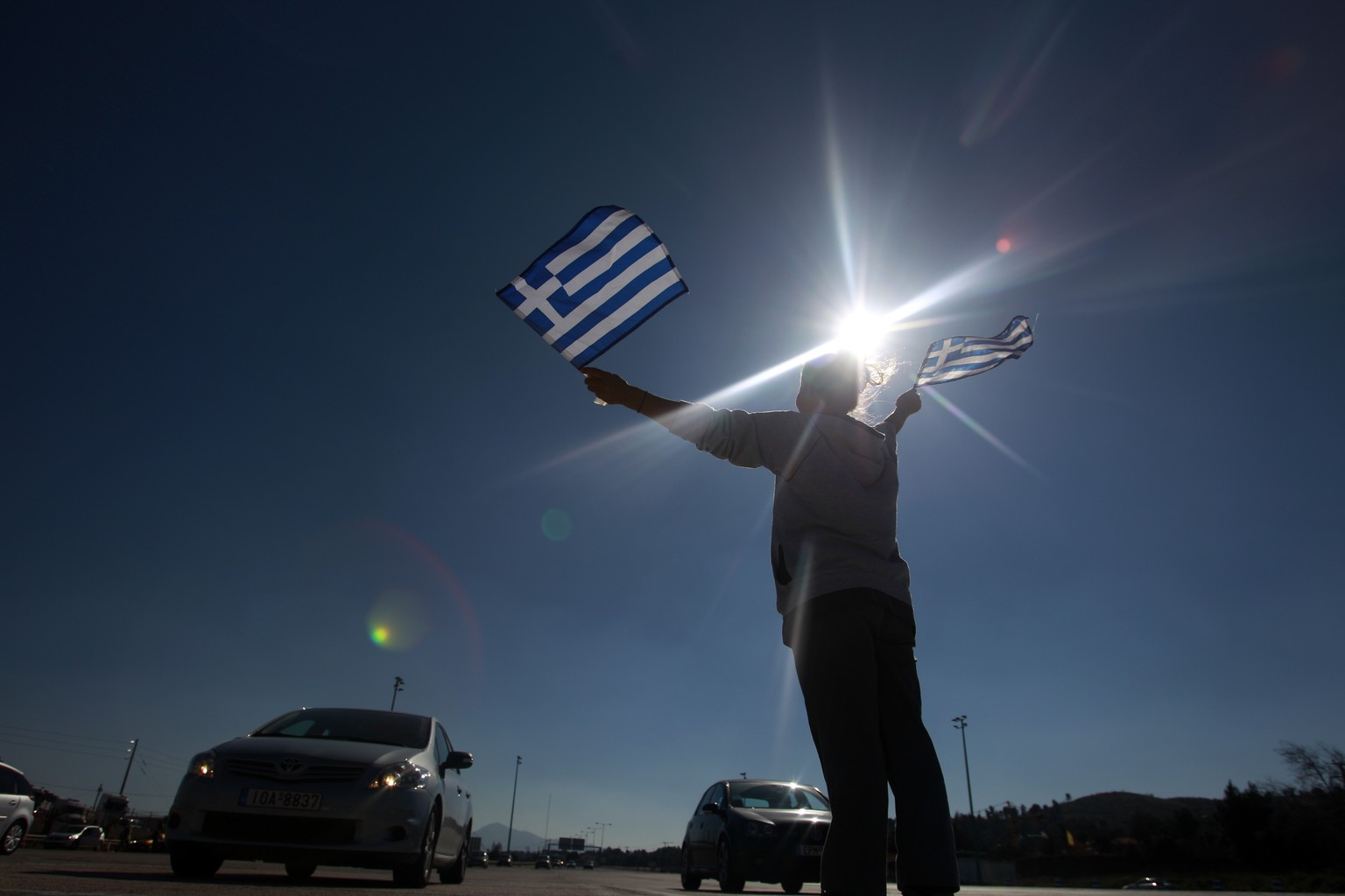 A protester raises Greek national flags to vehicles passing through without paying at the toll stations of Afidnes about 25 kilometers (12 miles) north of Athens, Sunday, Feb. 16, 2014. Hundreds of local residents of outlying Athens areas angered by new price increases for highway tolls took part in the rally. In the last couple of weeks drivers have started to pay 40-60 percent more on some sections of the Greek highway. (AP Photo/Kostas Tsironis)