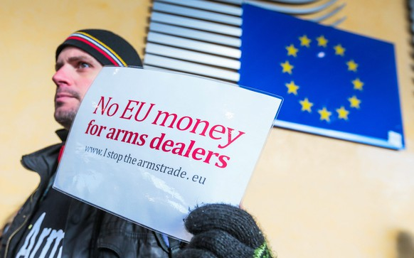 epa05625195 An activist holds a banner reading 'No EU money for arms dealers' to protest in front of the building of the European Commission against the subsidies of Europe in the armaments industry in Brussels, Belgium, 10 November 2016. Police decide to close the neighborhood as a measure of security.  EPA/STEPHANIE LECOCQ