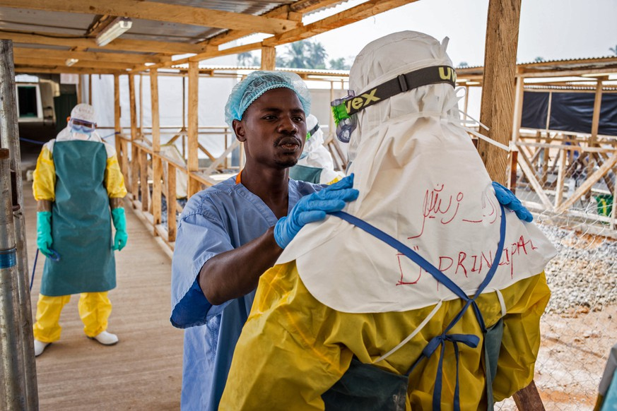 In this photo taken on Monday, March 2, 2015, a health care worker prepares a colleague's Ebola virus protective gear at an Ebola virus clinic operated by the International Medical Corps in Makeni, Sierra Leone. The World Health Organization says Thursday, March 12, 2015, its tally of Ebola deaths has passed the grim milestone of 10,000, mostly in West Africa.  (AP Photo/ Michael Duff)