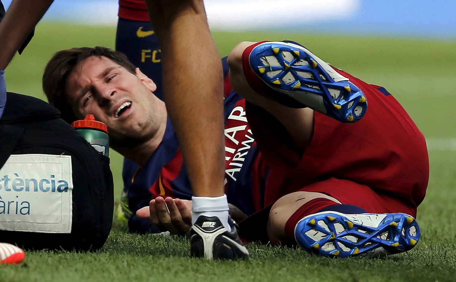 Barcelona's Lionel Messi grimaces as he lies on the pitch after injuring his left knee during their Spanish first division soccer match against Las Palmas at Camp Nou stadium in Barcelona, Spain, September 26, 2015. REUTERS/Sergio Perez