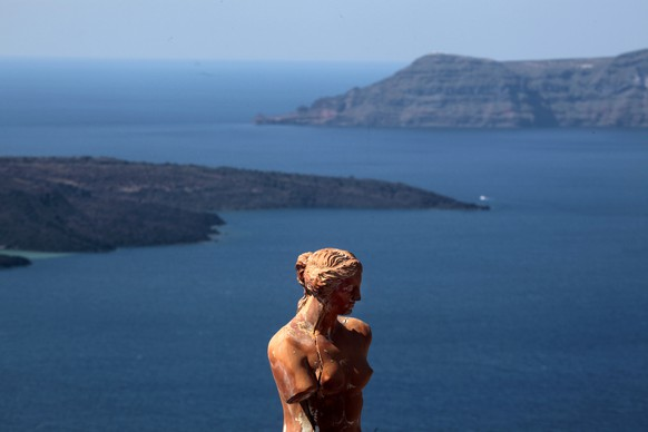 A replica of the ancient statue of Goddess Aphrodite of Milo is seen behind volcanic islets seen from the island of Santorini in the Aegean Sea, March 15, 2012. Initial data shows pre-bookings for the high summer season from Germany, which accounts for about 14 percent of Greece's total number of visitors, are down 20-30 percent. The drop in pre-bookings from Britain, Italy and the United States is expected to be smaller but still in the double-digit range. Greece's economy is in recession for a fifth consecutive year and is seen contracting by 4.3 percent this year as the government imposes austerity measures in exchange for financial aid from the European Union and the International Monetary Fund. REUTERS/Yannis Behrakis (GREECE - Tags: TRAVEL BUSINESS) - RTR2ZE6O