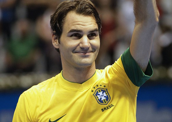 Switzerland's tennis player Roger Federer, wearing a Brazilian national team soccer jersey, waves to supporters at the end of a Gillette Federer Tour exhibition tennis match against Tommy Haas of Germany, in Sao Paulo, Brazil, Sunday, Dec. 9, 2012. (AP Photo/Andre Penner)