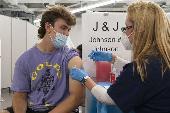 Bradley Sharp, of Saratoga, N.Y., gets the Johnson & Johnson vaccine from registered nurse Stephanie Wagner, Friday, July 30, 2021 in New York. Sharp needs the vaccination because it is required by his college. Amid increasing concern over the spread of the Delta variant, New York City announced on Wednesday that anyone can receive $100 if they get the first dose of the COVID-19 vaccine at any city-run vaccination clinic. (AP Photo/Mark Lennihan)