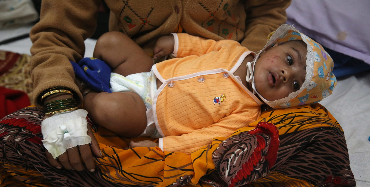 epa04337675 A three months old baby boy, who survived a landslide, receives treatment at the government hospital in Manchar, 65 kilometre from Malin village, Pune district, Maharashtra, India, 01 August 2014. At least fifty-one bodies have been found in the mounds of mud and stones left by the landslide that devastated the village of Malin in India's western state of Maharashtra. More than 360 personnel from the National Disaster Response Force were working in shifts assisted by local police and other officials.  EPA/DIVYAKANT SOLANKI