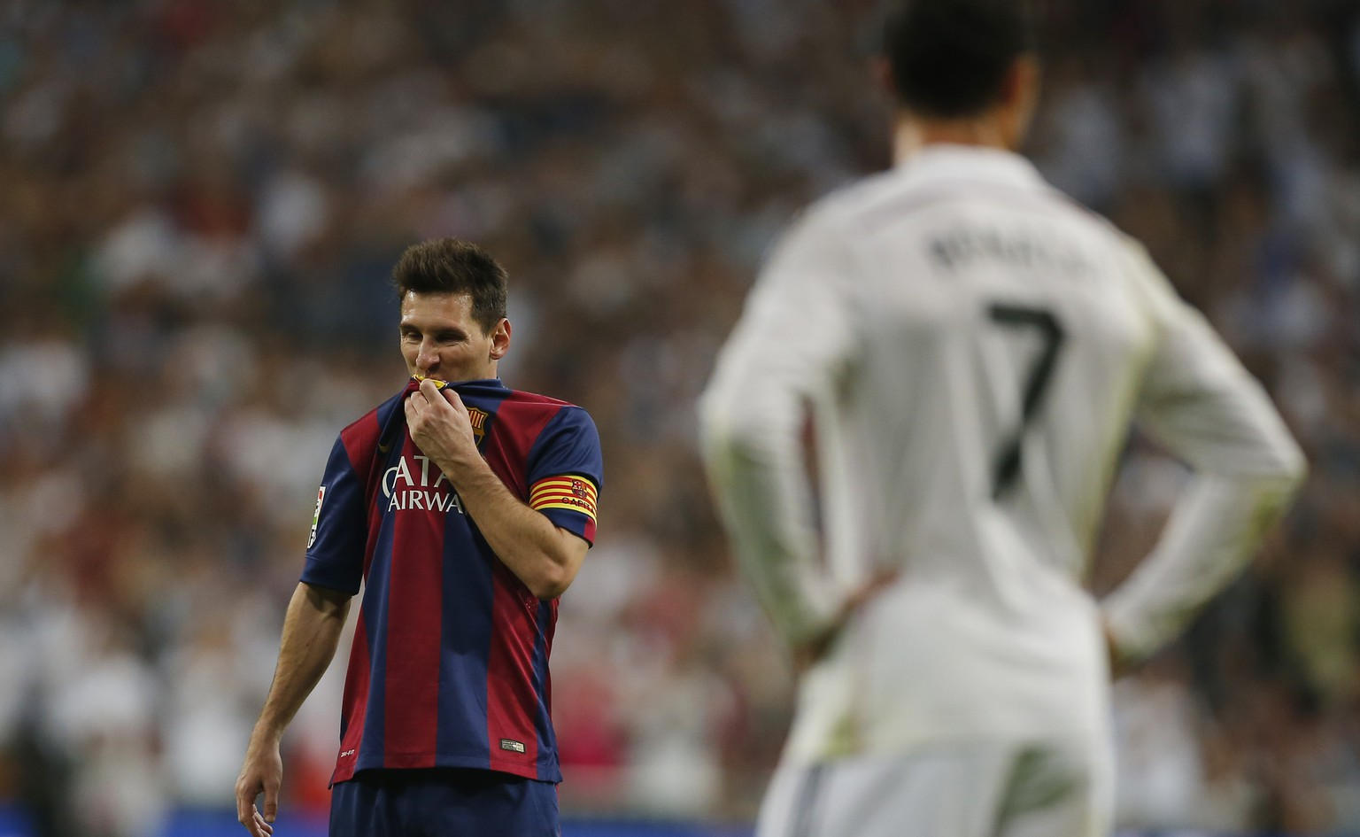Barcelona's Lionel Messi, left, gestures next to Real Madrid's Cristiano Ronaldo, right,  during a Spanish La Liga soccer match between Real Madrid and FC Barcelona at the Santiago Bernabeu stadium in Madrid, Spain, Saturday, Oct. 25, 2014. (AP Photo/Andres Kudacki)