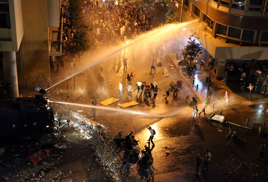 Lebanese activists shout anti-government slogans as they are sprayed by riot police using water cannons during a protest against the ongoing trash crisis, in downtown Beirut, Lebanon, Sunday, Aug. 23, 2015. Lebanese riot police are spraying thousands of protesters with water cannons in downtown Beirut, the second day of mass demonstrations against an ongoing trash crisis becoming violence. (AP Photo/Bilal Hussein)