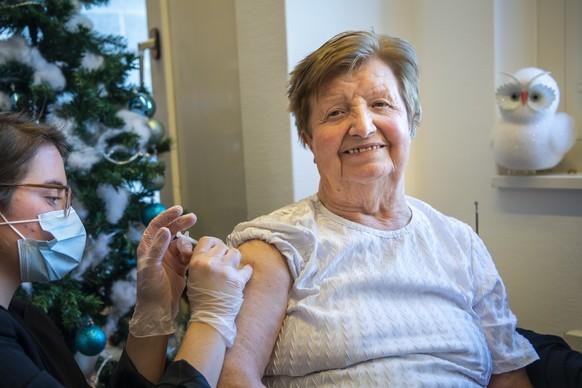 Une infirmiere donne la premiere dose du vaccin Pfizer-BioNTech a une residente fribourgeoise de l'EMS La Residence Saint-Martin a l'occasion du lancement de la vaccination contre le Sars-Cov-2 dans le canton de Fribourg lors de la crise du Coronavirus (Covid-19) le lundi 28 decembre 2020 a Cottens dans le canton de Fribourg. (KEYSTONE/Jean-Christophe Bott)