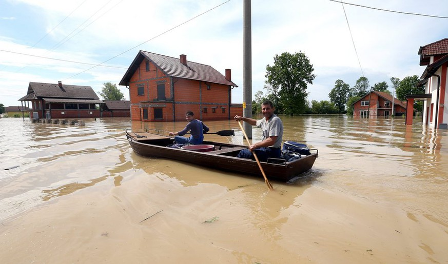 epa04215663 People are evacuated from their homes by boat in the city of Orasje, 250 km from the capital of Bosnia, Sarajevo, Bosnia and Herzegovina, 20 May 2014. A state of emergency has been declared in Bosnia and Herzegovina due to severe floods caused by rain falling for several days. Thousands of people in Bosnia, Serbia and Croatia were evacuated late 19 and early 20 May 2014 as rising floodwaters swallowed homes and farmland after last week's record rains.  EPA/FEHIM DEMIR