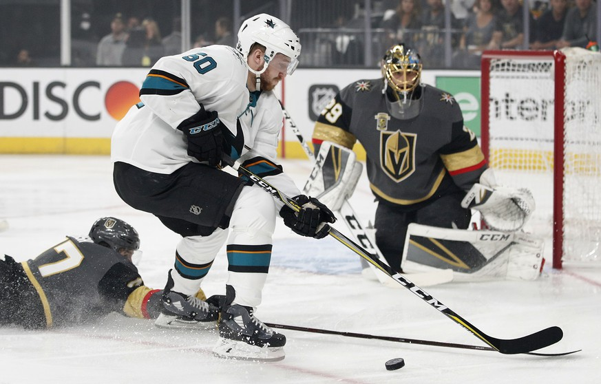 Vegas Golden Knights defenseman Luca Sbisa (47) knocks the puck away from San Jose Sharks center Chris Tierney during the first period of Game 5 of an NHL hockey second-round playoff series, Friday, May 4, 2018, in Las Vegas. (AP Photo/John Locher)