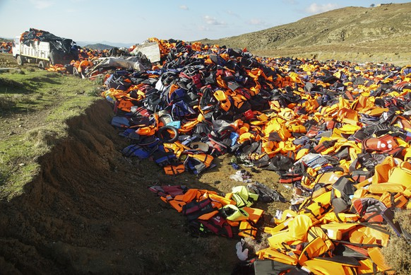 A Man unloads a truck filled with various life Jackets at the garbage area in the mountains of Lesbos Island, Greece, Monday, Jan. 25, 2016.  The buoyancy aides are discarded by migrants and collected from along the shore-line of the Greek island.  More than 850,000 people, most fleeing conflict in Syria and Afghanistan, entered Greece by sea in 2015, according to the UNHCR, and already in 2016, some 35,455 people have arrived despite plunging winter temperatures.(AP Photo/Mstyslav Chernov)