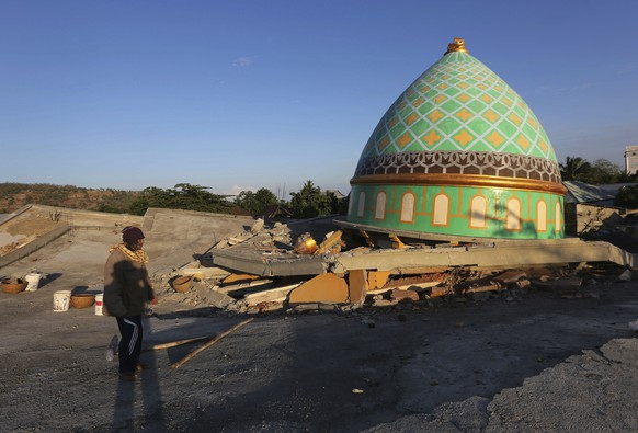 Locals view the devastation of a collapsed Jamiul Jamaah Mosque in Bangsal, North Lombok, Indonesia, Wednesday, Aug. 8, 2018. The north of Lombok was devastated by the powerful quake that struck Sunday night, damaging thousands of buildings and killing a large number of people. Rescuers were still struggling to reach all of the affected areas and authorities expect the death toll to rise. (AP Photo/Tatan Syuflana)