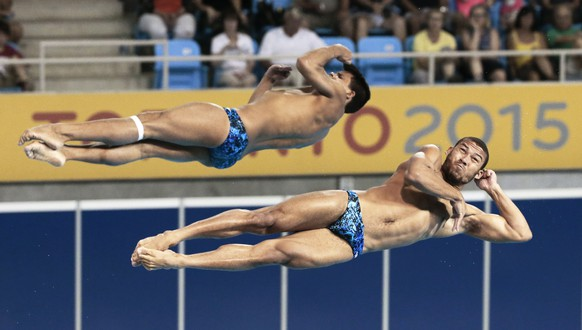 Edickson Contreras, top, and Robert Paez, bottom, of Venezuela, compete during the men's synchronized 3-meter springboard diving event at the Pan Am Games Monday, July 13, 2015, in Toronto. (AP Photo/Mark Humphrey)
