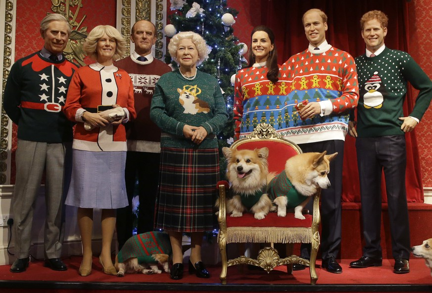 A dog owner tells her Pembrokeshire Welsh Corgi to 'stay' as four Corgi dogs pose next to wax work models of the British Royal family wearing colorful Christmas themed jumpers for a charity Christmas Jumper Day campaign at Madame Tussauds wax works in London, Tuesday, Dec. 6, 2016. The members of the royal family are from the left, Prince Charles Camilla, Duchess of Cornwall, Prince Phillip, Queen Elizabeth II, Kate, Duchess of Cambridge, Prince William, and Prince Harry.The Queen is well known for her love of this particular breed of dogs.(AP Photo/Alastair Grant)