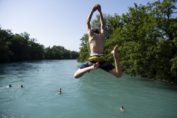 People jump from a bridge in the Aare River during the sunny and warm weather, in Bern. Switzerland, Wednesday, June 26, 2019. The forecasts predict hot weather in Switzerland with the maximum temperature at 38 degrees Celsius. (KEYSTONE/Anthony Anex)