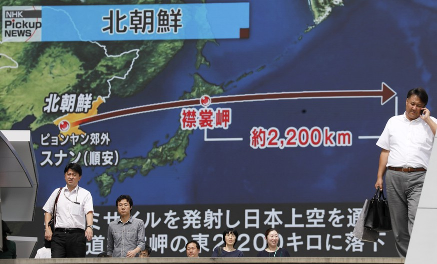 epa06205606 Pedestrians walk under a large-scale monitor displaying the flying course of a North Korean ballistic missile flying over Japan on a TV news broadcast in Tokyo, Japan, 15 September 2017. Earlier in the day, North Korea launched a ballistic missile over Japan that reportedly crashed in the Pacific Ocean, more than 2,000km east of the Japanese northern island of Hokkaido. There are no immediate reports of damage. According to reports quoting the South Korean and Japanese governments, the missile was purportedly fired from the North's capital Pyongyang. At the request of the USA and Japan, the United Nations (UN) Security Council will meet on 15 September.  EPA/KIMIMASA MAYAMA