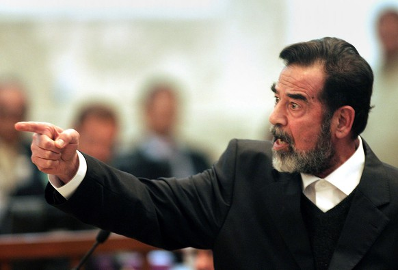 ADVANCE FOR SUNDAY DEC. 11 AND THEREAFTER - FILE - In this Jan. 29, 2006 file photo, former Iraqi president Saddam Hussein gestures during his trial in Baghdad, Iraq. In the beginning, it all looked simple: topple Hussein, destroy his purported weapons of mass destruction and lay the foundation for a pro-Western government in the heart of the Arab world. ¶   Nearly 4,500 American and more than 100,000 Iraqi lives later, the objective now is simply to get out _ and leave behind a country where democracy has at least a chance, where Iran does not dominate and where conditions may not be good but