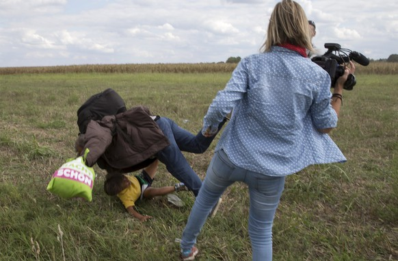 REFILE - ADDITIONAL INFORMATIONA migrant carrying a child falls after tripping on TV camerawoman (R) Petra Laszlo while trying to escape from a collection point in Roszke village, Hungary, September 8, 2015. Laszlo, a camerawoman for a private television channel in Hungary, was fired late on Tuesday after videos of her kicking and tripping up migrants fleeing police, including a man carrying a child, spread in the media and on the internet.  REUTERS/Marko Djurica
