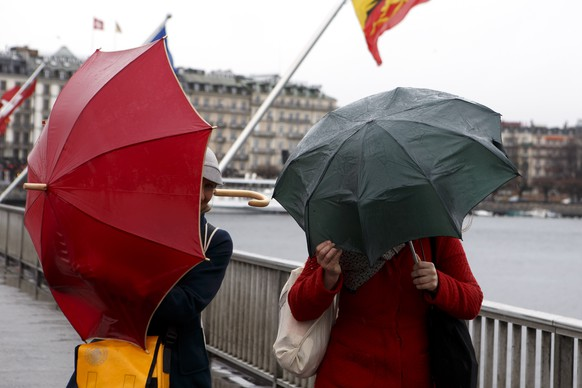 Pedestrians protect themselves with their umbrellas from the rain and of strong wind on the Mont Blanc bridge, which crosses the Lake Geneva, in Geneva, Switzerland, on Saturday, February 4, 2017. (KEYSTONE/Salvatore Di Nolfi)