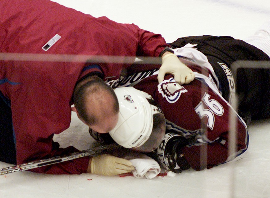 Colorado Avalanche forward Steve Moore is attended to by the team trainer after being injured in a fight with Vancouver Canucks Todd Bertuzzi during the third period of NHL action in Vancouver, British Columbia, Monday, March 8, 2004. A pool of blood formed around Moore's head as he lay motionless on the ice. A stretcher was wheeled out and after a delay of nearly 10 minutes Moore was taken off for medical attention. (AP Photo/Chuck Stoody)