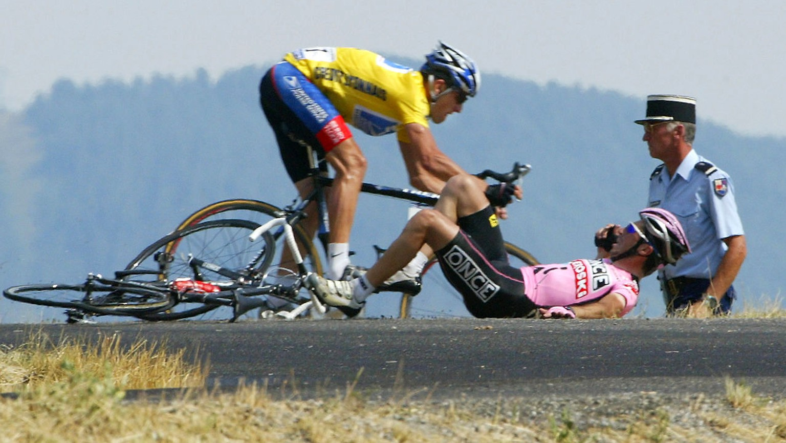 US Lance Armstrong (US Postal/USA) avoids Spaniard Joseba Beloki (ONCE/Spa) who fell down at the end of the ninth stage of the 90th Tour de France cycling race between Bourg d ´Oisans and Gap, 14 July 2003. AFP PHOTO JOEL SAGET