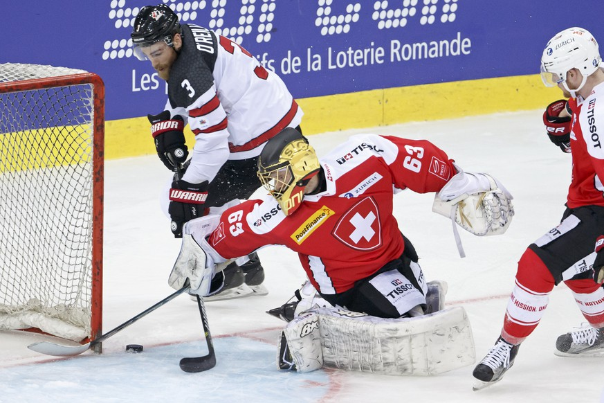 Canada's forward Ryan O'Reilly, left, vies for the puck with Switzerland's goaltender Leonardo Genoni, center, past Switzerland's forward Richard Tanner, right, during a friendly international ice hockey game between Switzerland and Canada, at the ice stadium Les Vernets, in Geneva, Switzerland, Tuesday, May 2, 2017. (KEYSTONE/Salvatore Di Nolfi)