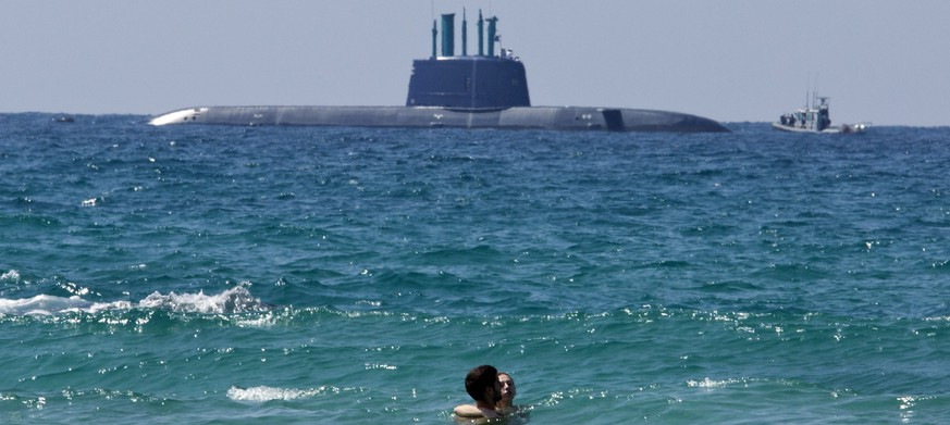 epa04413134 Israels new submarine, the fourth Dolphin-class submarine made in Germany, and called the INS Tanin, off shore   in south Haifa as it is met by Israeli navy vessels to make its last approach in its 20-day journey into haifa port, in northern Israel, 23 September 2014. The submarine let the German port of Kiel and traveled much of it's 8,000 kilometer journey underwater. The latest in Israeli submarine arsenal is said to be capable of firing nuclear warheads.  EPA/JIM HOLLANDER