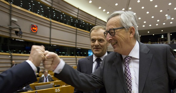 European Commission President Jean-Claude Juncker, right, bumps fists with an unidentified MEP during a plenary session at the European Parliament on Wednesday, March 25, 2015. The Energy Union, relations with Russia and the situation in Ukraine are up for a debate with the Commission and the Council on the conclusions of the March European Council. (AP Photo/Virginia Mayo)